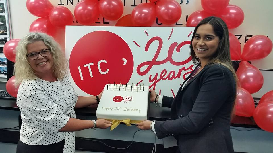 ITC Head of Group Services Michelle Chatfield and Student Services Advisor Sharon Roy pose with one of ITC's 20th birthday cakes.